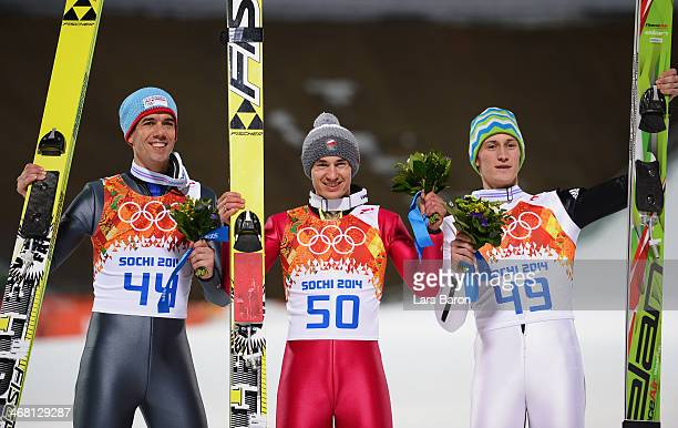 Bronze medalist Anders Bardal of Norway gold medalist Kamil Stoch of Poland and silver medalist Peter Prevc of Slovenia pose after the flower...