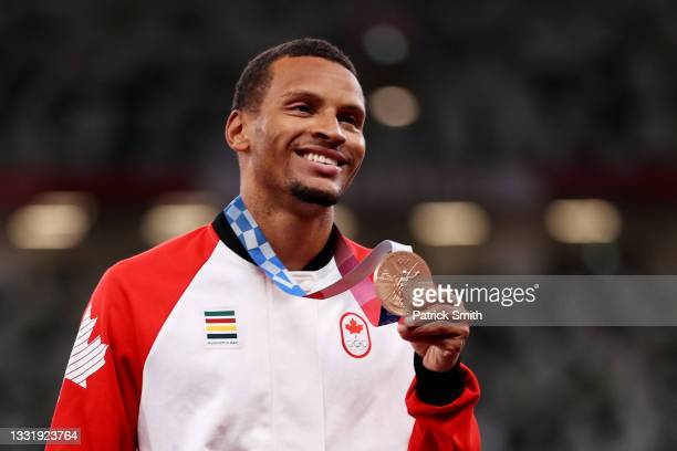 Bronze medalist Andre De Grasse of Team Canada holds up his medal on the podium during the medal ceremony for the Men's 100m on day ten of the Tokyo...