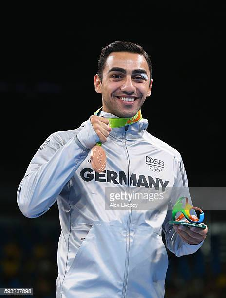 Bronze medalist Artem Harutyunyan of Germany poses on the podium during the medal ceremony for the Men's Boxing Light Welter on Day 16 of the Rio...