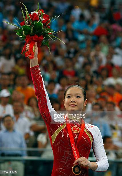 Bronze medalist Cheng Fei of China waves to the crowd from the podium during the medal ceremony for the Women's Beam Final at the National Indoor...