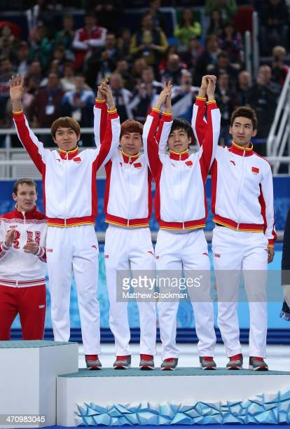 Bronze medalist China celebrate on the podium during the flower ceremony for the Men's 5000m Relay on day fourteen of the 2014 Sochi Winter Olympics...
