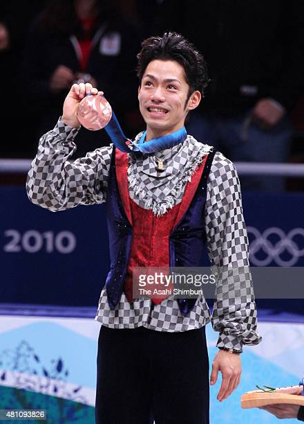 Bronze medalist Daisuke Takahashi of Japan celebrates on the podium at the medal ceremony for the Figure Skating Men's Singles during day seven of...