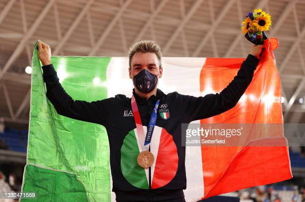 Bronze medalist Elia Viviani of Team Italy, pose on the podium while holding the flag of their country during the medal ceremony after the Men's...