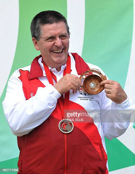 Bronze medalist England's Michael Gault poses on the podium during the award ceremony for the men's 10m Air Pistol shooting event during the 2014...