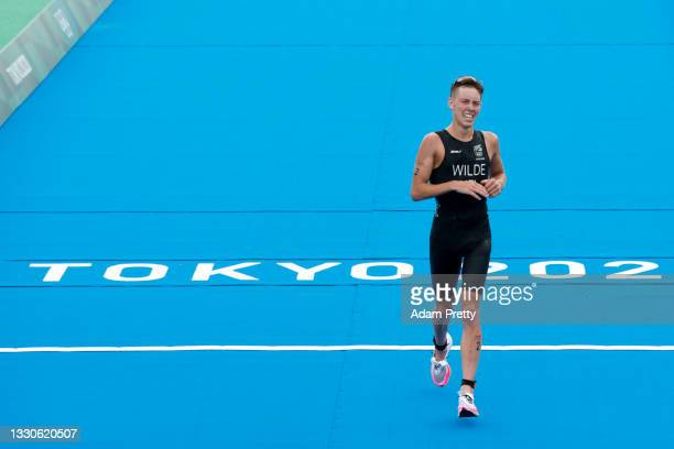 Bronze medalist Hayden Wilde of Team New Zealand reacts as he crosses the finish line during the Men's Individual Triathlon on day three of the Tokyo...