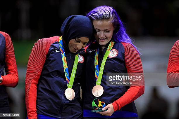 Bronze medalist Ibtihaj Muhammad of the United States celebrates on the podium with Dagmara Wozniak of the United States during the Women's Sabre...