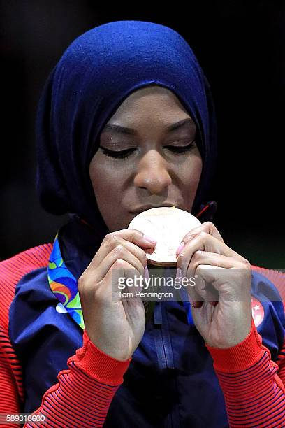 Bronze medalist Ibtihaj Muhammad of the United States celebrates on the podium during the Women's Sabre Team bronze medal match between United States...