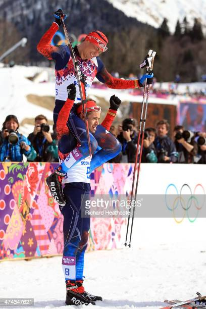 Bronze medalist Ilia Chernousov of Russia picks up gold medalist Alexander Legkov of Russia after the Men's 50 km Mass Start Free during day 16 of...