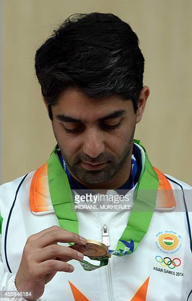 Bronze medalist India's Abhinav Bindra checks his medal after the medal ceremony of the men's 10m air rifle individual event at the Ongnyeon...
