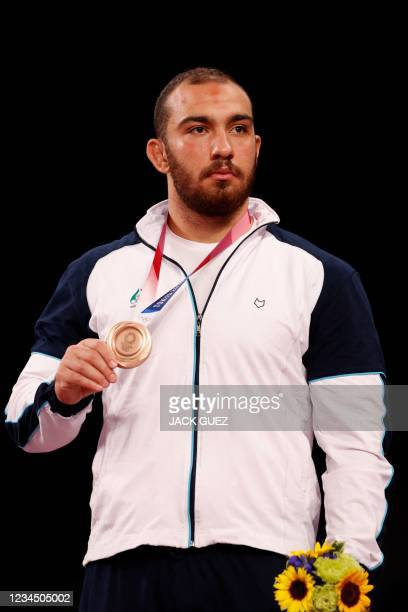 Bronze medalist Iran's Amir Hossein Zare poses with his medal on the podium after the men's freestyle 125kg wrestling competition during the Tokyo...