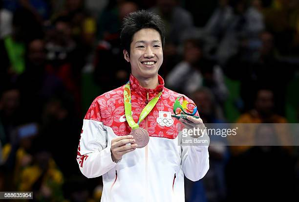 Bronze medalist Jun Mizutani of Japan poses on the podium during the medal ceremony for the Mens Table Tennis Gold Medal match between Ma Long of...