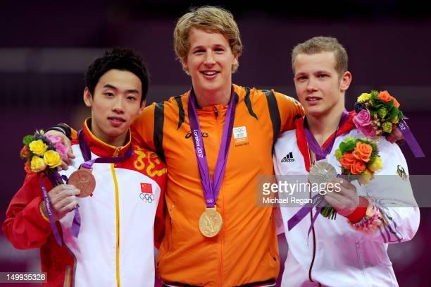 Bronze medalist Kai Zou of China gold medalist Epke Zonderland of Netherlands and silver medalist Fabian Hambuchen of Germany pose on the podium...