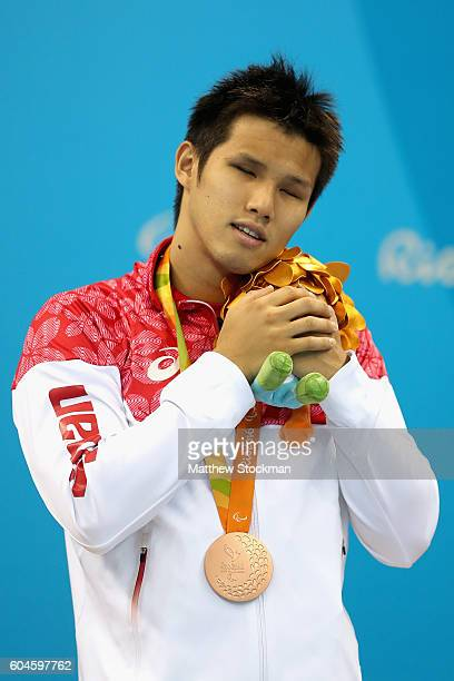 Bronze medalist Keiichi Kimura of Japan celebrates on the podium at the medal ceremony for the Mens 100m Breaststroke SB11 Final during day 6 of the...