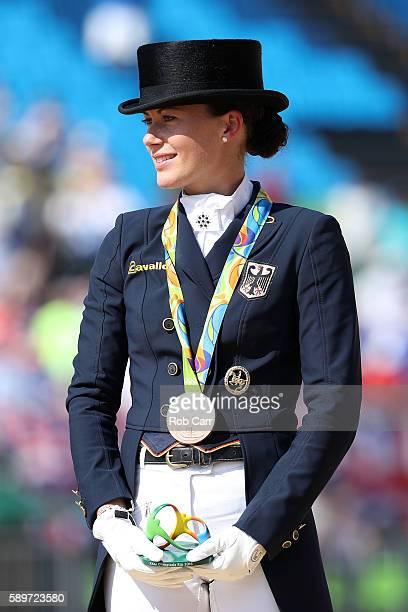 Bronze medalist, Kristina Broring-Sprehe of Germany riding Desperados Frh celebrates on the podium during the medal ceremony of the Dressage...