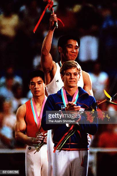 Bronze medalist Li Ning of China gold medalist Koji Gushiken of Japan and silver medalist Peter Vidmar of the United States pose on the podium at the...