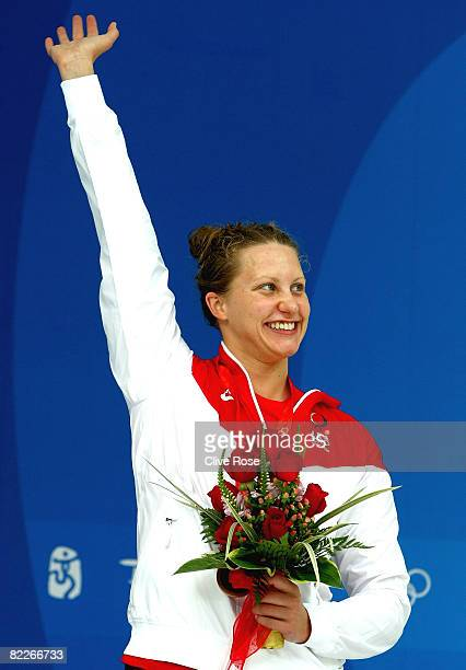 Bronze medalist Margaret Hoelzer of the United States waves from the podium during the medal ceremony for the Women's 100m Backstroke held at the...