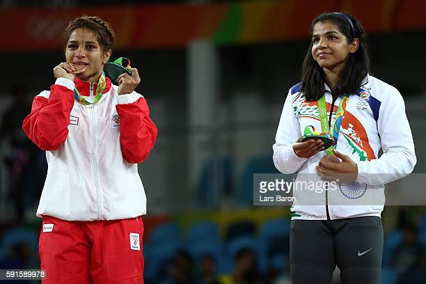 Bronze medalist Marwa Amri of Tunisia and bronze medalist Sakshi Malik of India stand on the podium during the medal ceremony after the Women's...