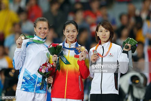 Bronze medalist Olga Safronova of Kazakhstan gold medalist Wei Yongli of China and Silver medalist Chisato Fukushima of Japan pose on the podium...