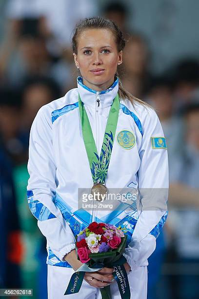 Bronze medalist Olga Safronova of Kazakhstan pose on the podium during the victory ceremony for the Women's 100m during day nine of the 2014 Asian...