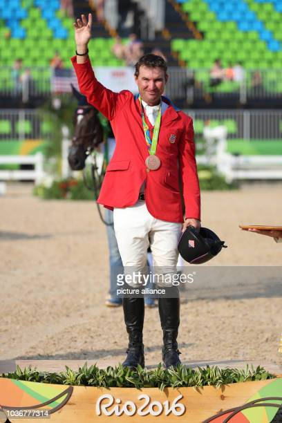 Bronze medalist Phillip Dutton of USA celebrates on the podium after the Eventing Individual Jumping of the Equestrian events during the Rio 2016...