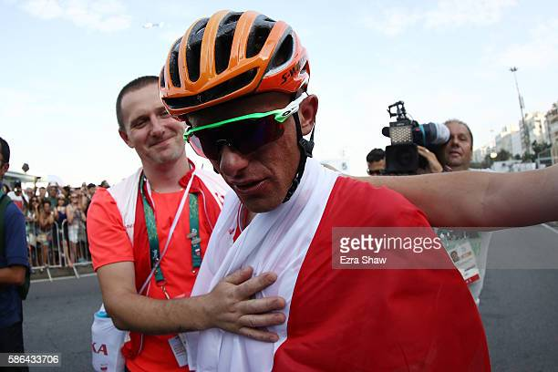 Bronze medalist Rafal Majka of Poland is consoled after the Men's Road Race on Day 1 of the Rio 2016 Olympic Games at the Fort Copacabana on August...