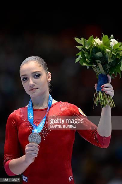 Bronze medalist Russian gymnast Aliya Mustafina celebrates on the podium of the all around final at the 44th Artistic Gymnastics World Championships...