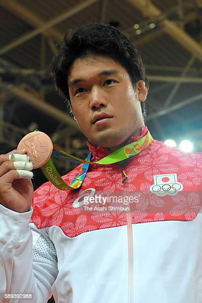 Bronze medalist Ryunosuke Haga of Japan poses for photographs after the medal ceremony for the men's 100kg on Day 6 of the 2016 Rio Olympics at...