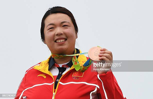 Bronze medalist Shanshan Feng of China poses on the podium during the medal ceremony for Women's Golf on Day 15 of the Rio 2016 Olympic Games at the...