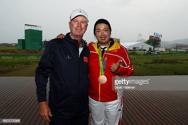 Bronze medalist Shanshan Feng of China poses with her caddie after Women's Golf on Day 15 of the Rio 2016 Olympic Games at the Olympic Golf Course on...