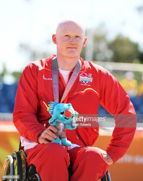 Bronze medalist Simon Lawson of England looks on during the medal ceremony for the Men's T54 marathon on day 11 of the Gold Coast 2018 Commonwealth...