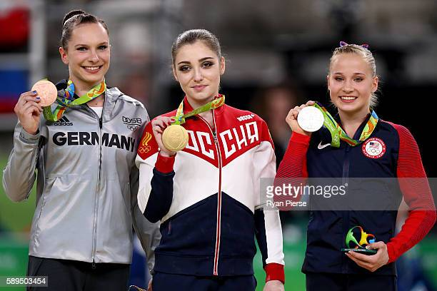 Bronze medalist Sophie Scheder of Germany gold medalist Aliya Mustafina of Russia and silver medalist Madison Kocian of the United States pose for...