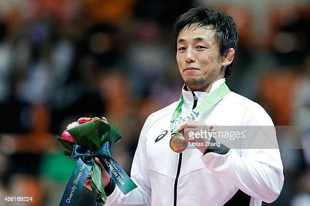 Bronze medalist Takafumi KoJima of Japan celebrates during the medal ceremony after Wrestling Men's Freestyle 70 kg Gold Medal Final during day eight...