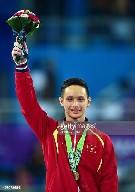 Bronze medalist Vietnam's Phuong Thanh Dinh poses during the medal ceremony of the men's parallel bars final of the artistic gymnastics event at the...