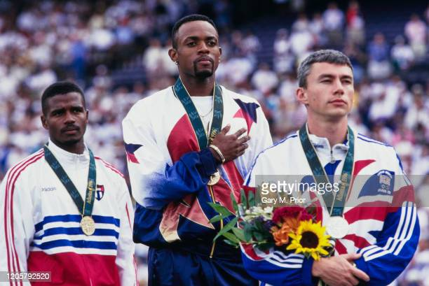 Bronze medalist Yoelbi Quesada from Cuba gold medalist Kenny Harrison from the United States and Jonathan Edwards from Great Britain stand on the...