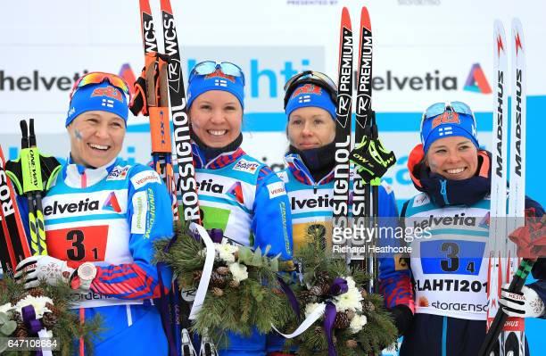 Bronze medalists AinoKaisa Saarinen Kerttu Niskanen Laura Mononen and Krista Parmakoski of Finland celebrate during the flower ceremony for the...