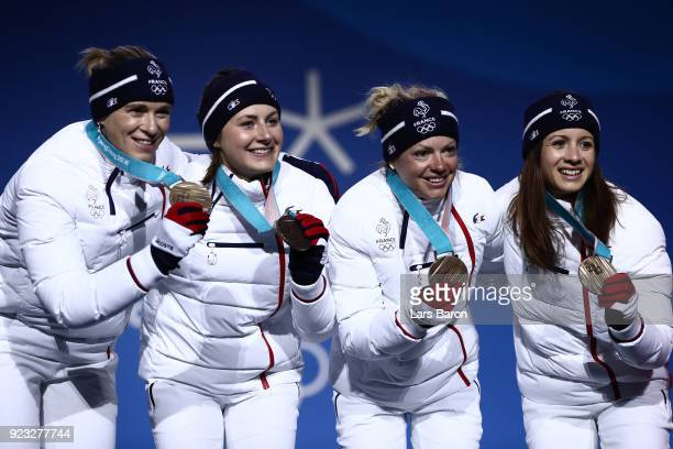 Bronze medalists Anais Chevalier Marie Dorin Habert Justine Braisaz and Anais Bescond of France celebrate during the medal ceremony for Biathlon...