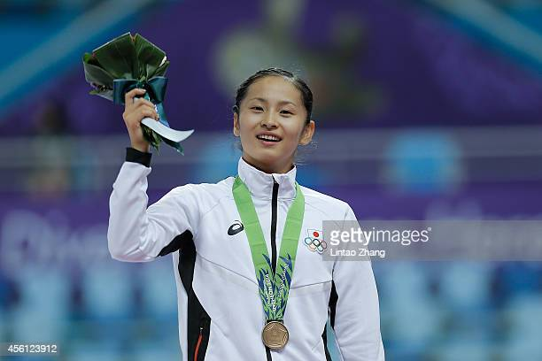 Bronze medalists Ayano Kishi of Japan celebrates during the medal ceremony after the Gymnastics Trampoline Women's Final in day seven of the 2014...