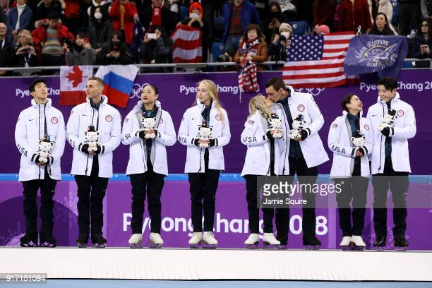 Bronze medalists Chris Knierim and Alexa Scimeca Knierim kiss on the podium as Team United States celebrate in the victory ceremony after the Figure...