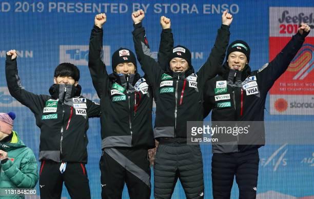 Bronze medalists Daiki Ito Ryoyu Kobayashi Junshiro Kobayashi and Yukiya Sato of Japan celebrate during the medal ceremony for the Men's Team Ski...