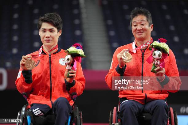 Bronze medalists Daiki Kajiwara and Hiroshi Murayama of Team Japan celebrate on the podium at the medal ceremony for the Badminton Men's Doubles WH...