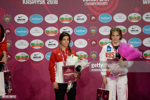Bronze medalists Evin Demirhan of Turkey and Milana Dadasheva of Russia on stage after competing in the women's 50 kg category within the 2018...