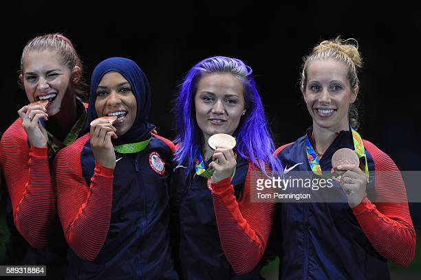 Bronze medalists Ibtihaj Muhammad Mariel Zagunis Monica Aksamit and Dagmara Wozniak of the United States celebrate on the podium after winning the...