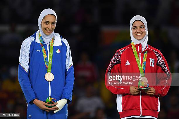 Bronze medalists Kimia Alizadeh Zenoorin of the Islamic Republic of Iran and Hedaya Wahba of Egypt celebrate on the podium after the Women's 57kg...