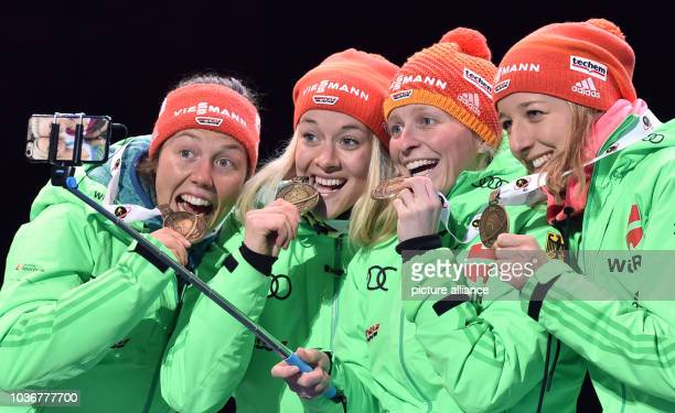 Bronze medalists Laura Dahlmeier Maren Hammerschmidt Franziska Hildebrand and Franziska Preuss of Germany show their medals into the smartphone...