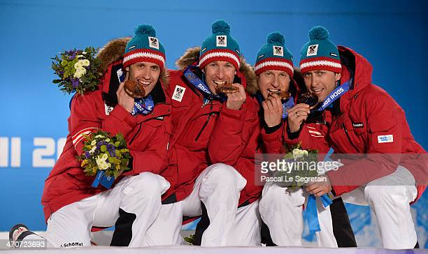 Bronze medalists Lukas Klapfer, Bernhard Gruber, Mario Stecher and Christoph Bieler of Austria celebrate during the medal ceremony for the Nordic...