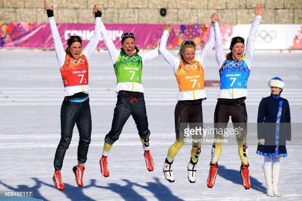 Bronze medalists Nicole Fessel, Stefanie Boehler, Claudia Nystad, Denise Herrmann of Germany celebrate on the podium during the flower ceremony for...
