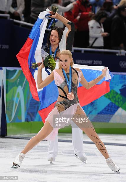 Bronze medalists Oksana Domnina and Maxim Shabalin of Russia do a victory lap with Russian flags after the 2010 Winter Olympics ice dance figure...