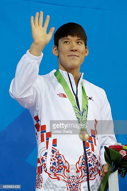 Bronze medalists Park Taehwan of South Korea celebrate during the medal ceremony after the swimming Men's 400m Freestyle Final during the day four of...