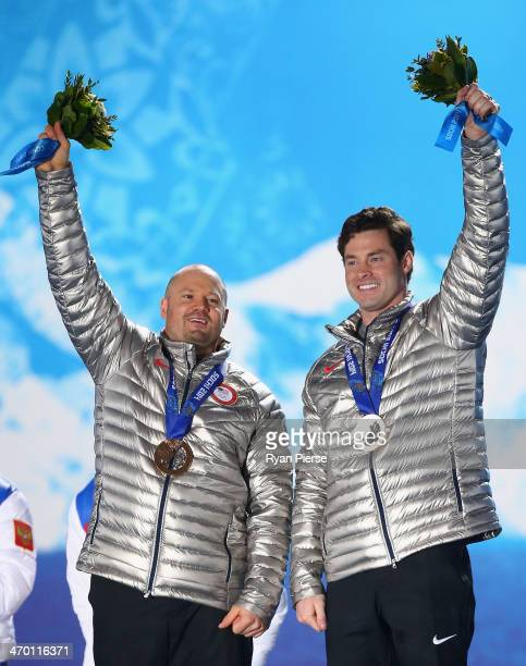 Bronze medalists Steven Holcomb and Steven Langton of the United States team 1 celebrate on the podium during the medal ceremony for the Men's TwoMan...