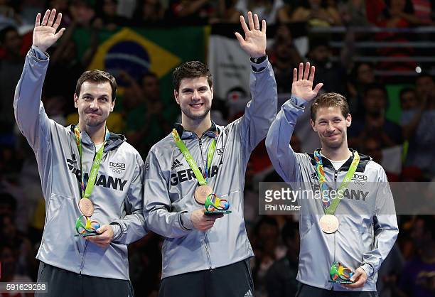 Bronze medalists Timo Boll Dimitrij Ovtcharov and Bastian Steger of Germany celebrate on the podium during the Men's Team Table Tennis medal ceremony...